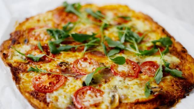 Pizza, ilmakuivattua kinkkua, minimozzarellaa ja rucolaa